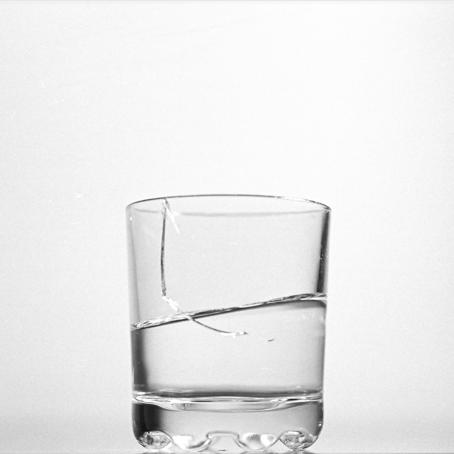 A white background with a glass cup. The cup is filled with water and has a small crack in it.