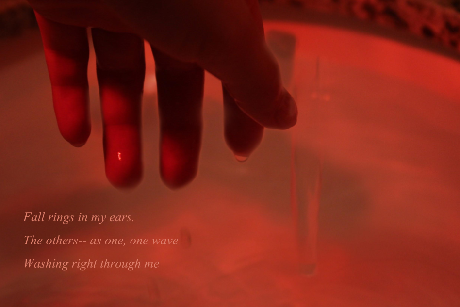 Photo Haiku. Red tones and a hand dripping with water. There is text displayed that read the poem.