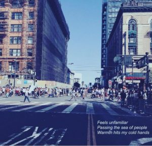 """A large crowd of people walking through a crosswalk, with two large buildings on the left and left. Haiku on bottom left of the photo that says, """"Feels unfamiliar, passing the sea of people, warmth hits my cold hands."""""""
