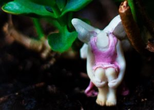 Photo depicting a small clay headless fairy with white wings sitting in a huddled position next to a green plant.