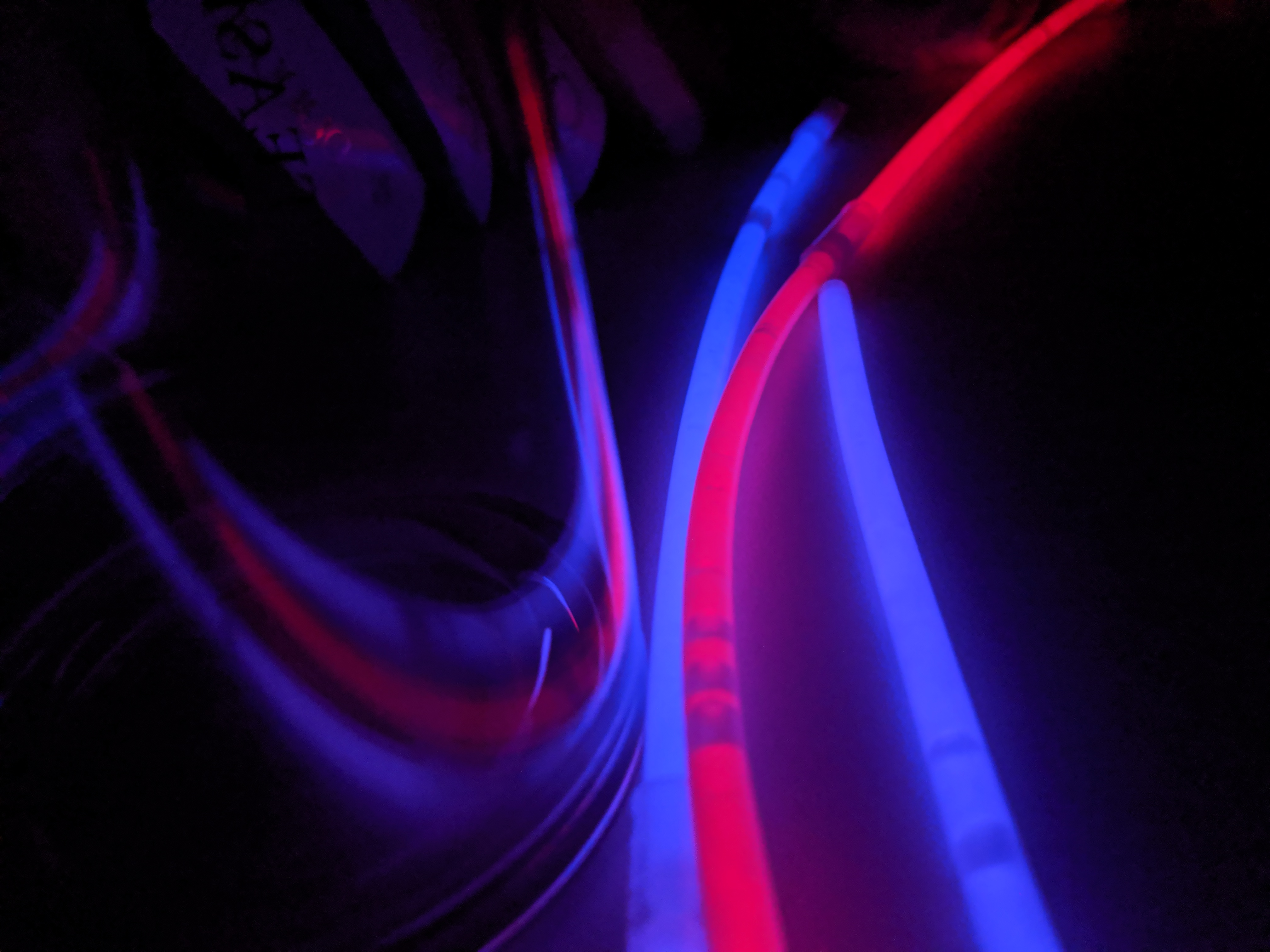 An almost abstract image of glowing glowsticks reflecting on a clear surface in the dark,creating multiple leading lines.