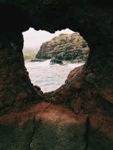 Photo of a rock with the shape of a heart cut through it. The ocean and waves are seen through the heart shaped cutout.