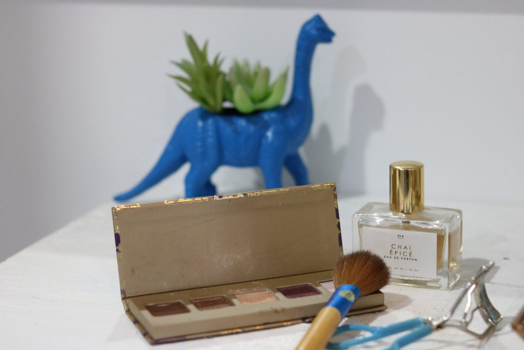 a makeup palette, makeup brush, eyelash curler, perfume and succulent plant