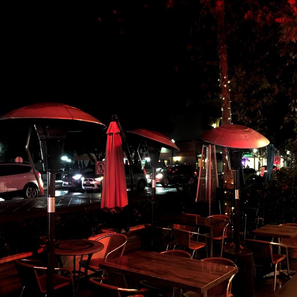 Streetside dining lit in red lights.