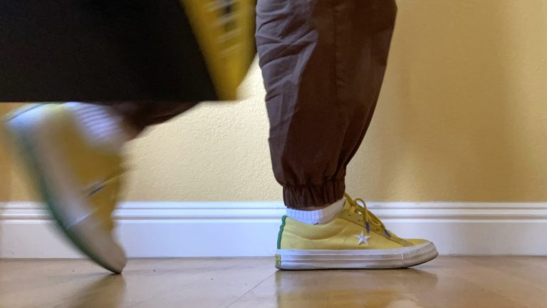 A pair of feet walking by carrying a bag. Yellow and brown colors are complemented by white.