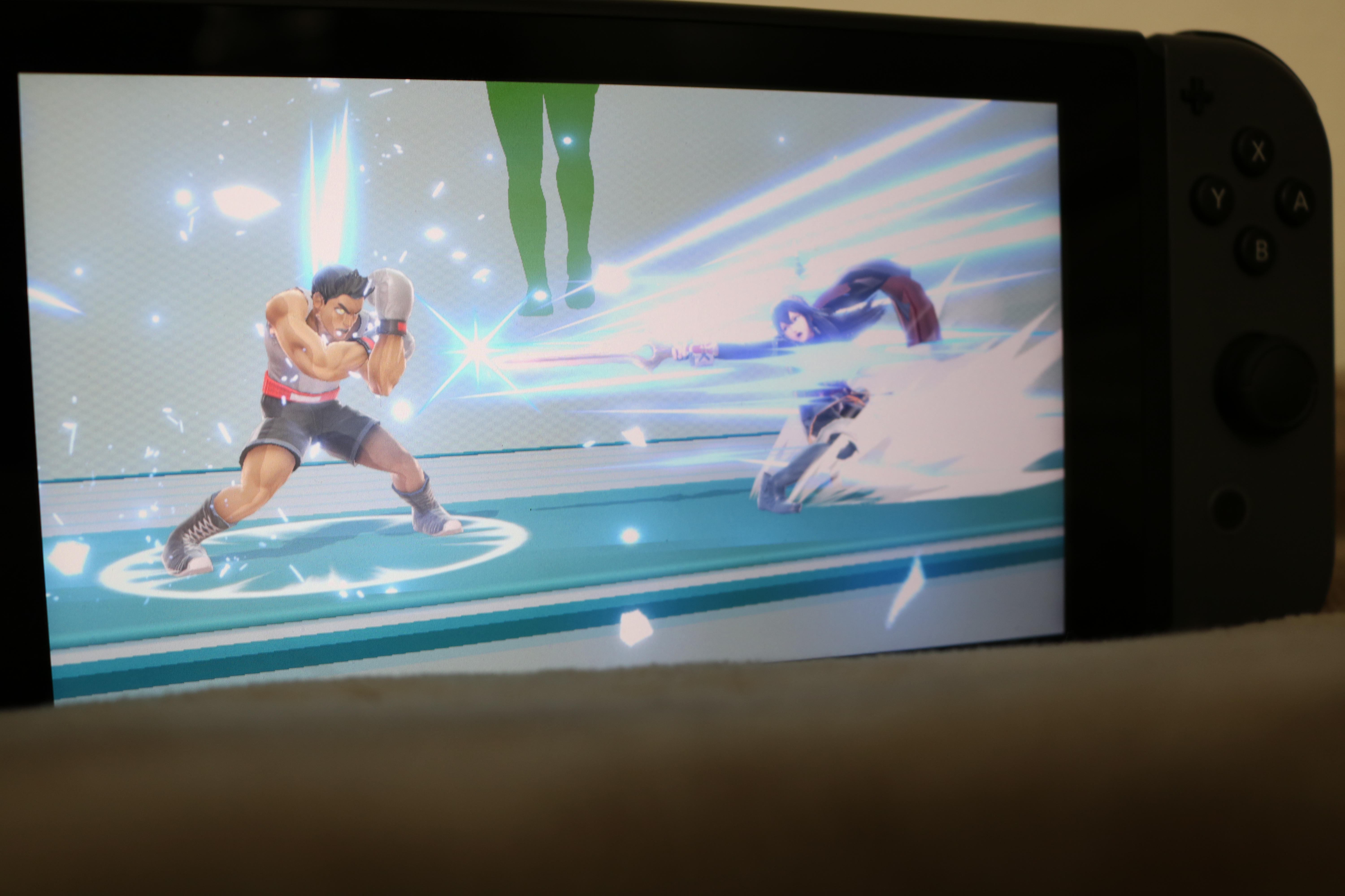 Photo of a Nintendo Switch. with an image of a battle between Little Mac and Lucina on the screen.