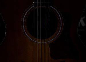 Close up of the center of a guitar in the dark
